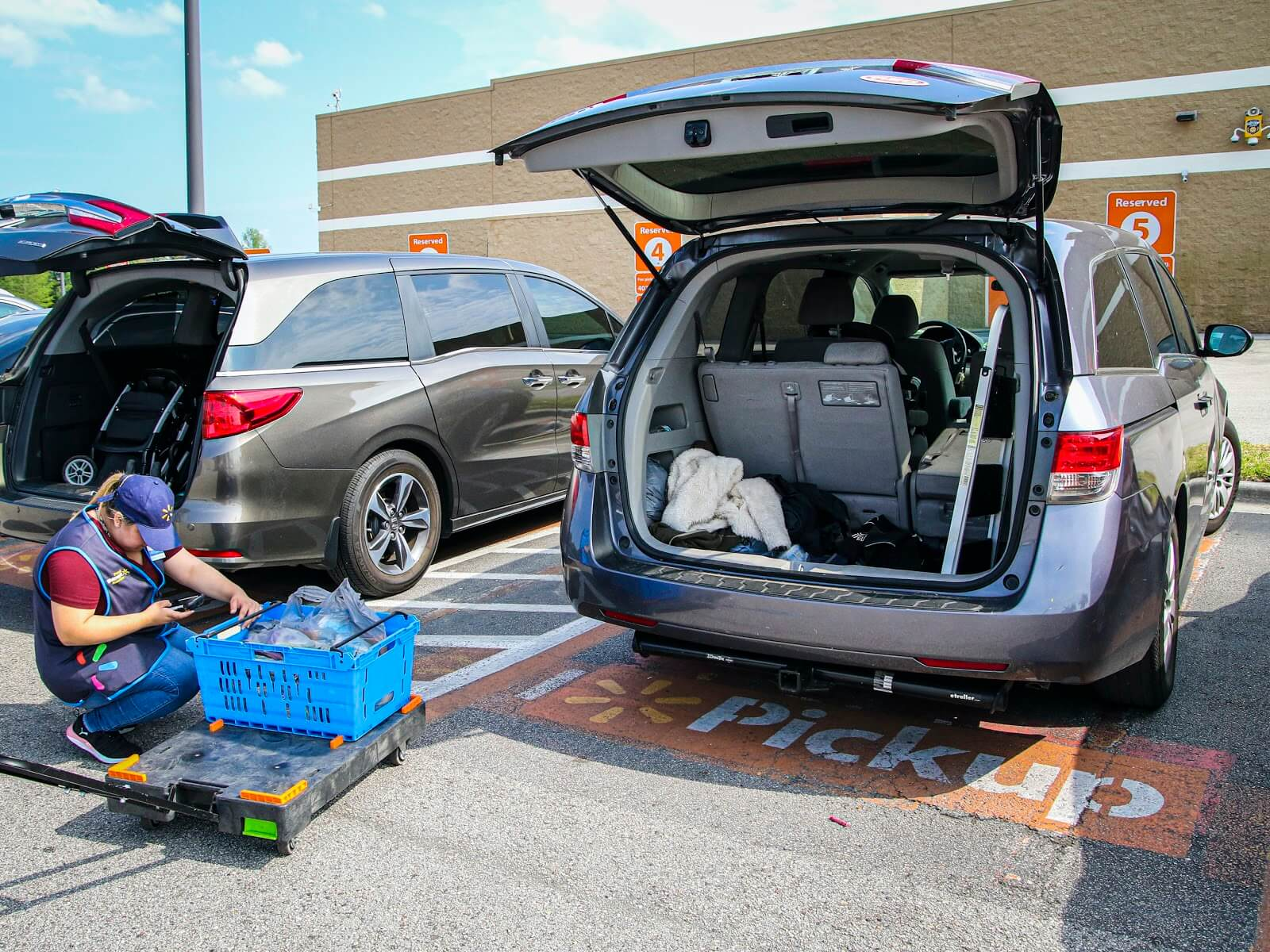 BOPIS retail: as shown here at Walmart with an employee loading up two mini-vans with BOPIS groceries.