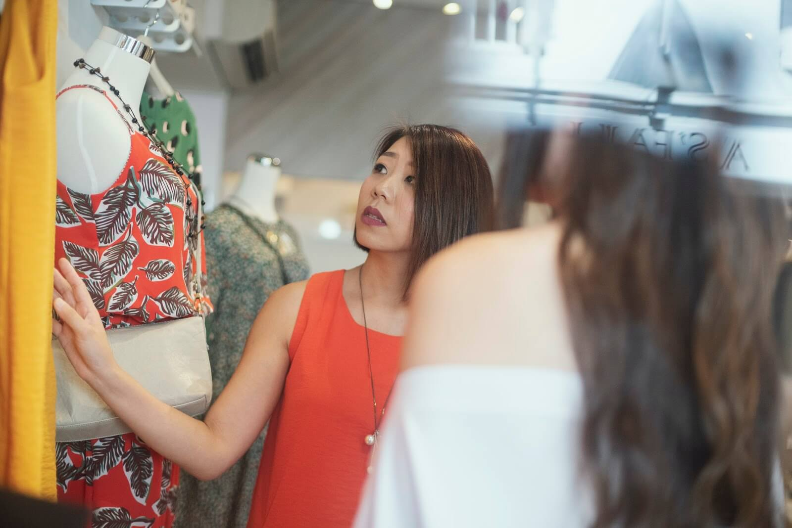 eCommerce POS Integration: A retail store owner is working on the clothing displays in her store.